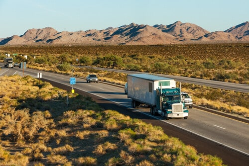 A large truck on a highway with a desert landscape
