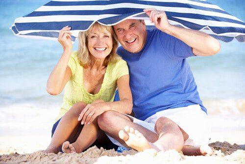 An older couple sitting on a beach under a striped umbrella